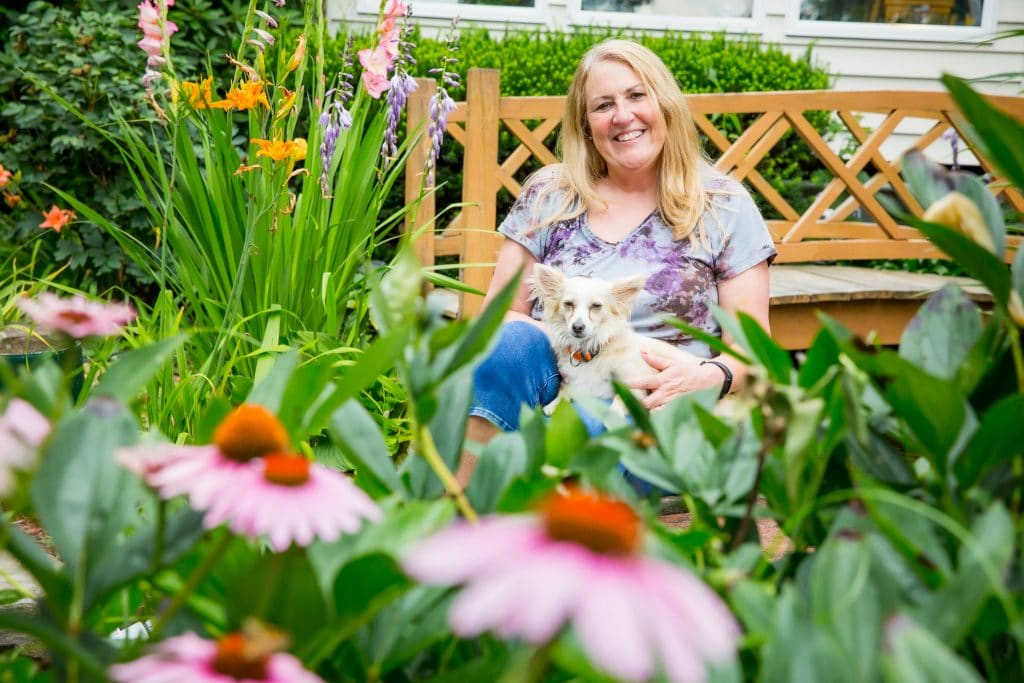 Genny Resch and her dog relaxing in their back yard